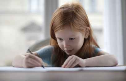 clever focused little girl doing homework at home